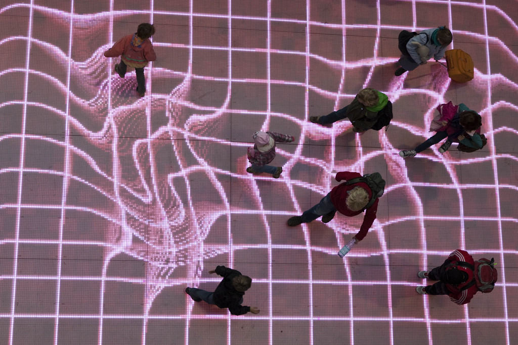 "People walk over the interactive installation ""Onskebronn"", Norwegian for wishing well, at A central station in Berlin, Germany, Thursday, Oct. 14, 2010. The moving paths of visitors are followed on that LED-platform and retraced as reprocessed projections directly onto the floor. Sound is triggered by the movement of interacting visitors as they step onto the platform. The installation is created by German Sven Beyer of the performing arts group ""Phase 7"". (AP Photo/Gero Breloer)"