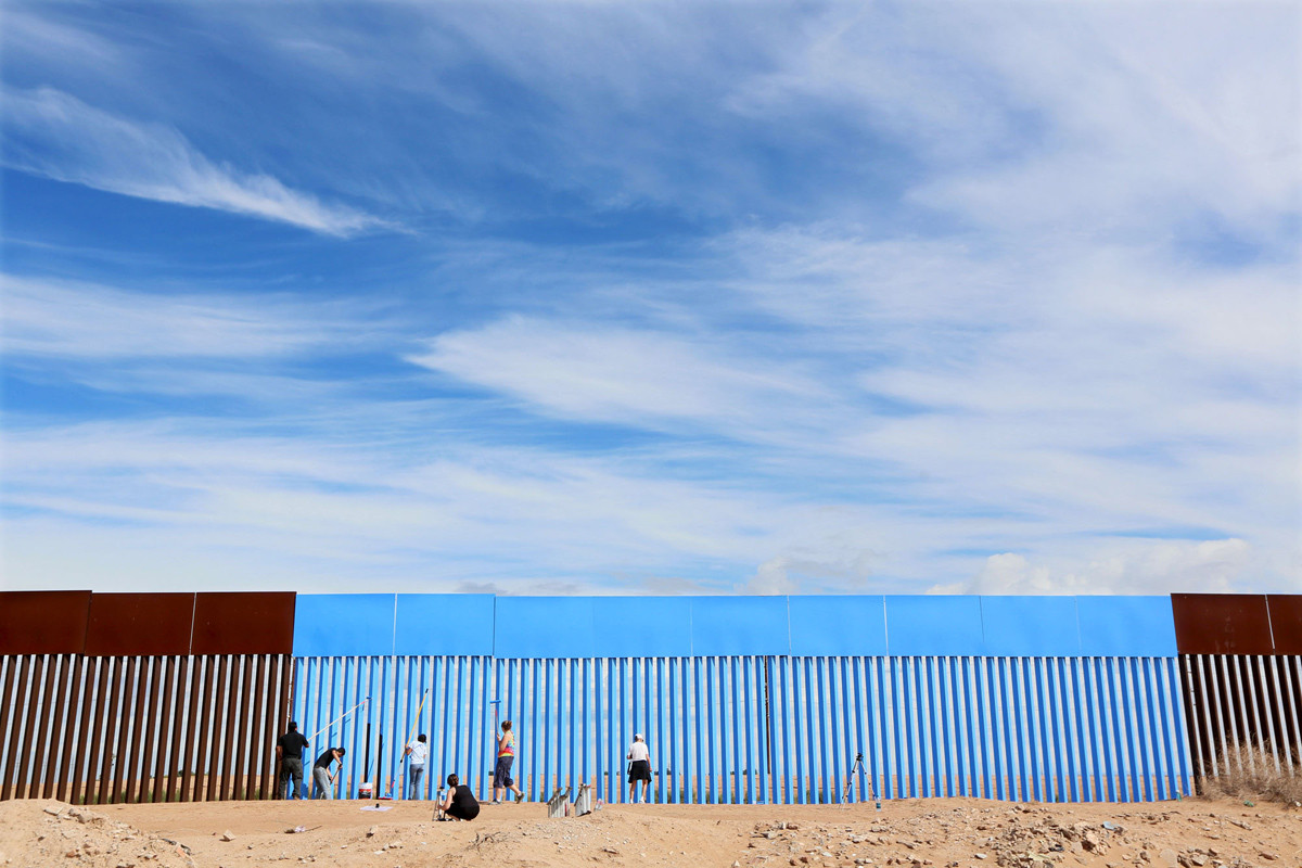 "Volunteers paint the border fence between the United States and Mexico to give the illusion of transparency during the ""Borrando la Frontera"" (Erasing the Border) Art Project in Mexicali, Mexico April 9, 2016. REUTERS/Sandy Huffaker FOR EDITORIAL USE ONLY. NOT FOR SALE FOR MARKETING OR ADVERTISING CAMPAIGNS TPX IMAGES OF THE DAY - RTX298P8"