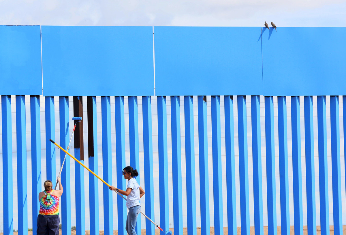 "Volunteers Brooke Collins (L) and Ana Lucia Lopez paint the border fence, while two doves sit on top of the wall between the United States and Mexico, to give it the illusion of transparency during her ""Borrando la Frontera"" (Erasing the Border) Art Project of Ana Teresa Fernandez, in Mexicali, Mexico April 9, 2016. REUTERS/Sandy Huffaker FOR EDITORIAL USE ONLY. NOT FOR SALE FOR MARKETING OR ADVERTISING CAMPAIGNS - RTX298QN"